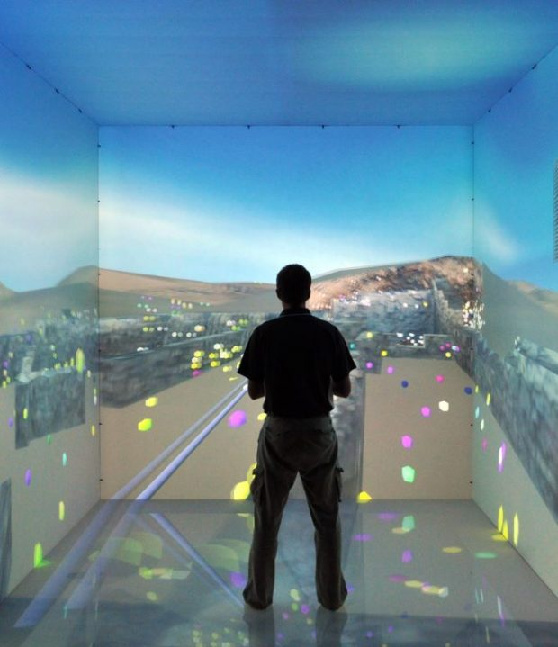 A person inside a cave virtual reality environment is surrounded on five sides by a computer generated representation of an archaeological dig site in Egypt